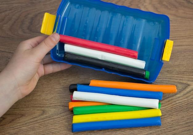 Руки маленькой девочки вынимают разноцветную глину