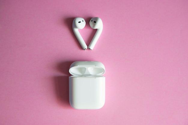 オープン充電器の上に横になっている白いワイヤレスヘッドフォン