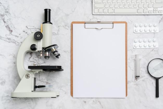 トップビューから机の上の顕微鏡の生物学と化学の主題