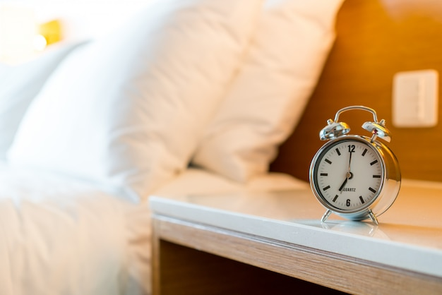 白い寝室に金属の目覚まし時計