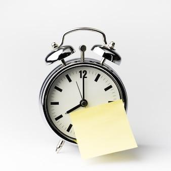 白い背景の上の付箋紙メモ付き目覚まし時計