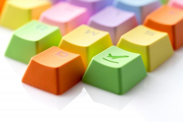 オンライン予約の概念のためのコンピューターのキーボード上のカラフルな旅行アイコン