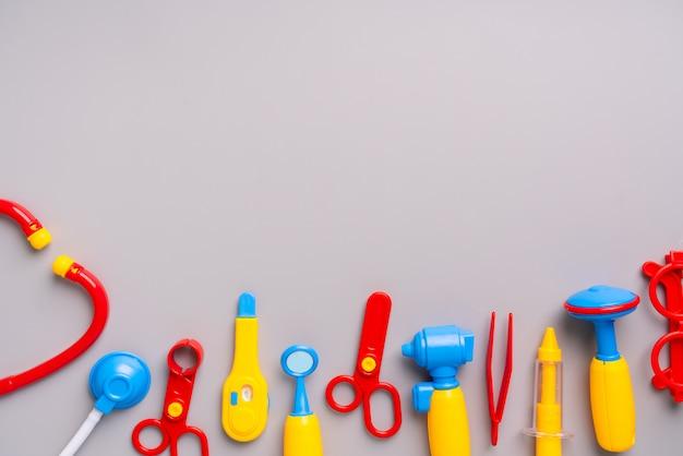 医師は、フラットレイアウトの創造的な教育概念で子供のためのおもちゃを設定