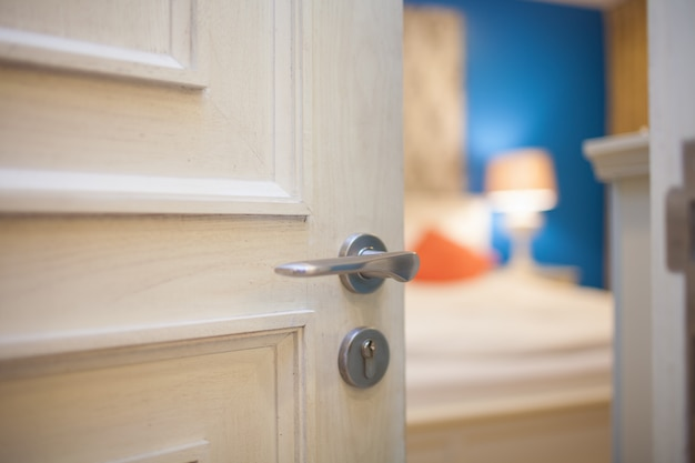 ホテルおよび家の概念のための寝室のドアを開く手