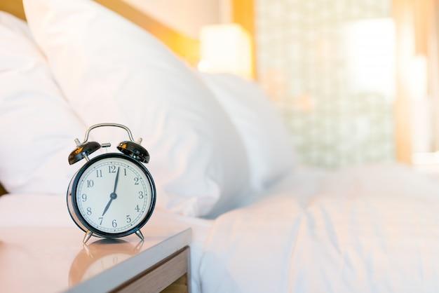 白い寝室に金属製の目覚まし時計