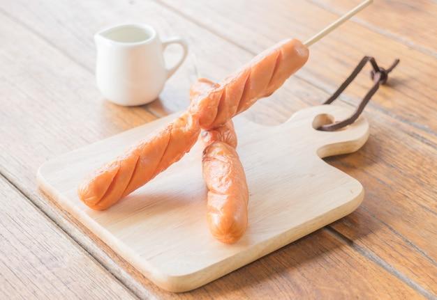 ポークホットドッグ、木製のプレートで焼く