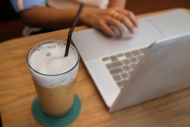 木製のテーブルにミルクコーヒーを飲むのガラス