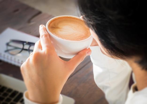仕事のテーブルでコーヒーのカップに手を