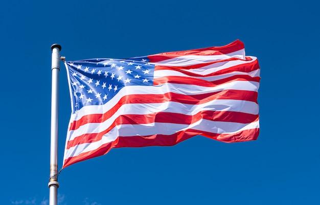 アメリカの国旗と青い空、旗竿、ニューヨークに手を振るアメリカの国旗
