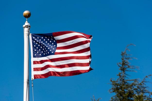 青い空を背景に手を振るアメリカの国旗、米国旗を振る