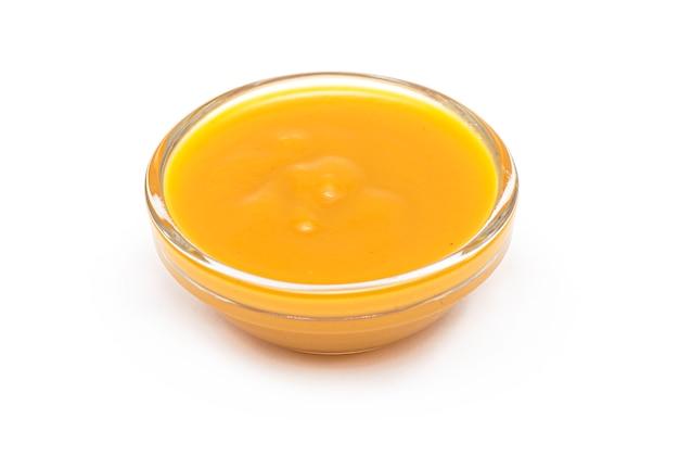 ガラスのボウル、白で隔離されるマンゴーフルーツのピューレのマンゴーピューレ