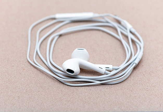 テキストまたはアイデア、ワイヤー、イヤホン用のスペースを持つ柔らかい茶色の紙に白いヘッドフォン