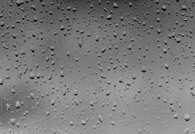 背景として黒いガラスに雨の滴