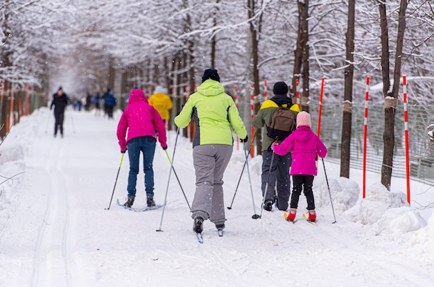 Семья катается на лыжах в общественном парке в удивительный зимний день