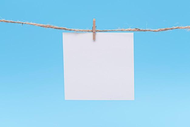 Чистый лист бумаги, висящий на веревке булавкой