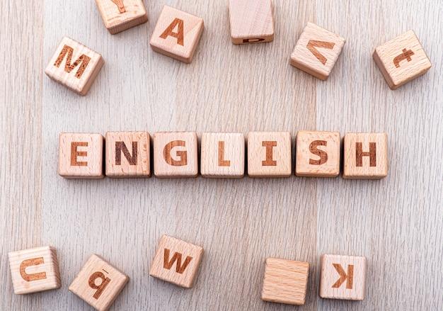 木製のテーブル、木製のキューブ、英語と教育についての概念図による英語の単語