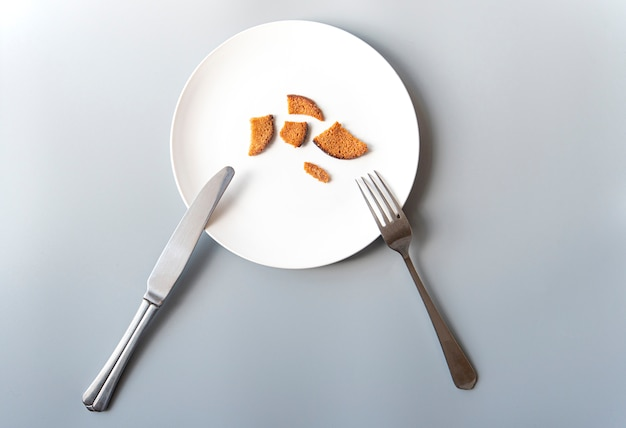 Белая тарелка с крекерами, ножом и вилкой, бедность, банкротство, голод, концептуальная картина
