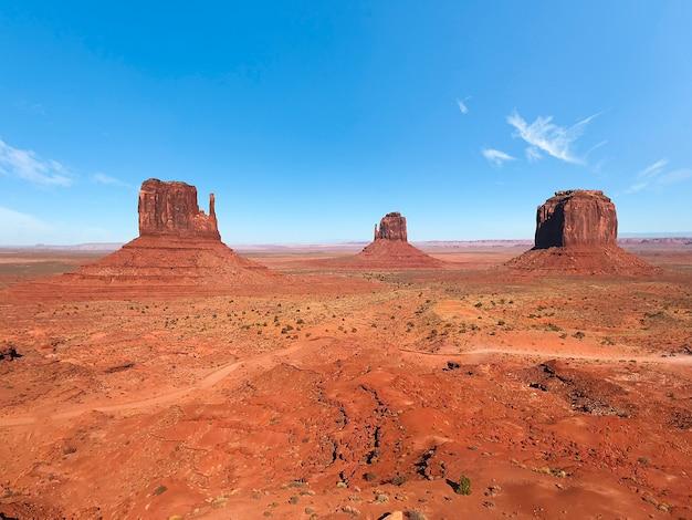 赤い砂漠と青い空と雲の朝のモニュメントバレーの素晴らしい景色。アリゾナ州のモニュメントバレー、ウェストミトンビュート、イーストミトンビュート、メリックビュート。