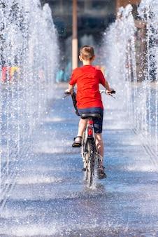 少年は、都市公園の噴水の間を自転車に乗って子供。ロシア、モスクワのゴーリキーパークで通りに自転車の少年