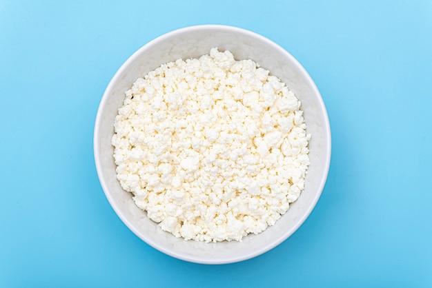 青いテーブルの上の白いボウルに新鮮なカッテージチーズ。プレート上の牛乳カード。上面図。