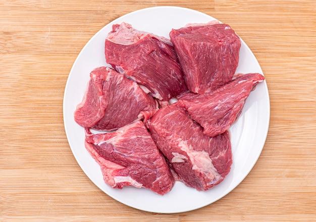 白いプレート、トップビューでバーベキューやグーラッシュ肉の牛肉の生の大きな部分