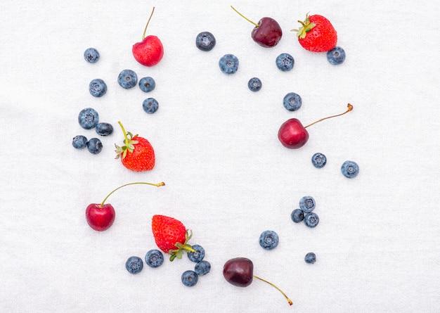 ベリー入り夏:チェリー、イチゴ、ブルーベリーまたはビルベリーと白い表面にブラックベリー