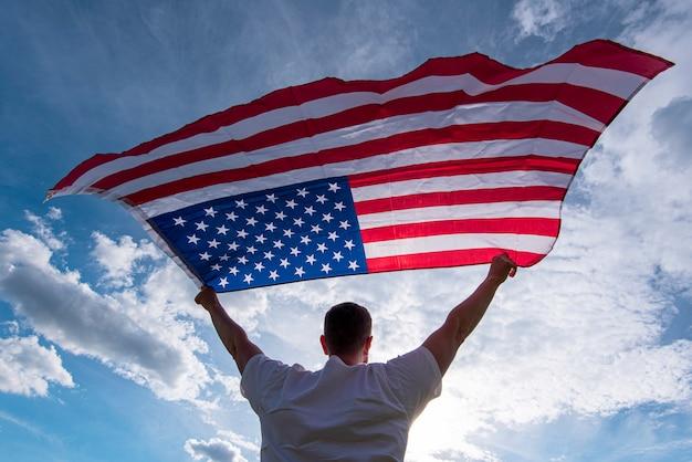 アメリカ、コンセプト画像の手でアメリカの旗を振って保持している男
