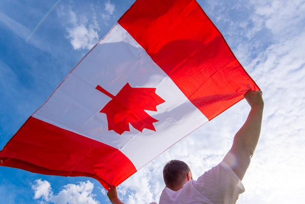 Мужчина держит национальный флаг канады против голубого неба