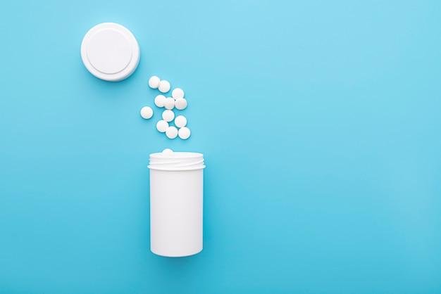 Медицинское образование с белой бутылкой и таблетки на синей поверхности, вид сверху