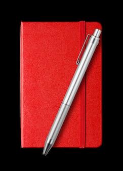Красная закрытая тетрадь и ручка на черном фоне