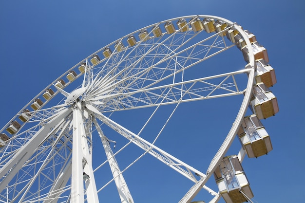 遊園地の青い空を背景に観覧車