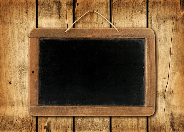 木製の壁の背景に黒板