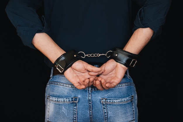 革の手錠で背中の後ろに白人の手