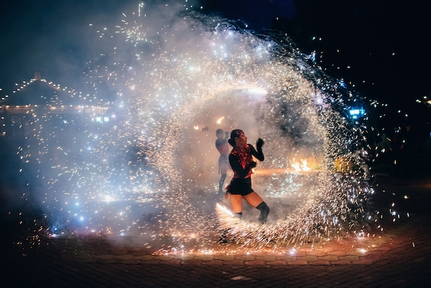 ファイヤーショー。女の子は燃えるような輝くトーチを回転させる