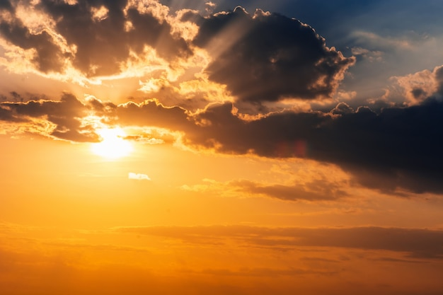 雲の切れ間から太陽光線が付いている空の美しい黄金の夕日
