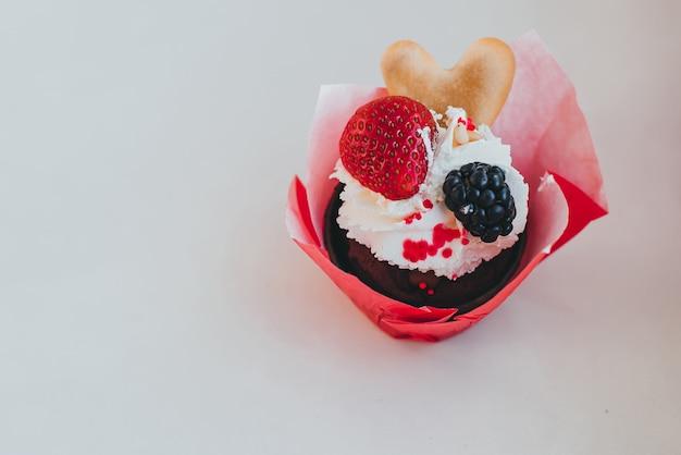 クリームと新鮮な甘いイチゴの果実とブラックベリーのカップケーキ