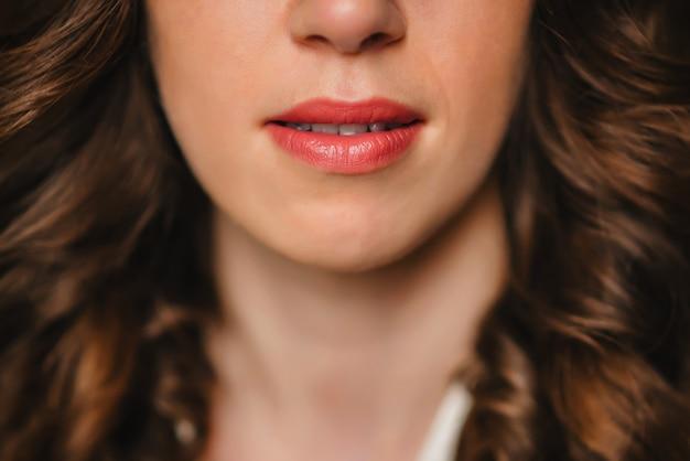 赤い口紅で魅力的な女の子の唇をクローズアップ