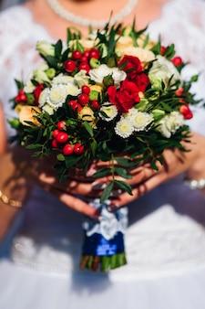 赤いバラと花嫁の手に白いヒナギクのウェディングブーケ