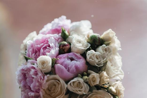 Свадебный букет с белыми и розовыми пионами с каплями дождя
