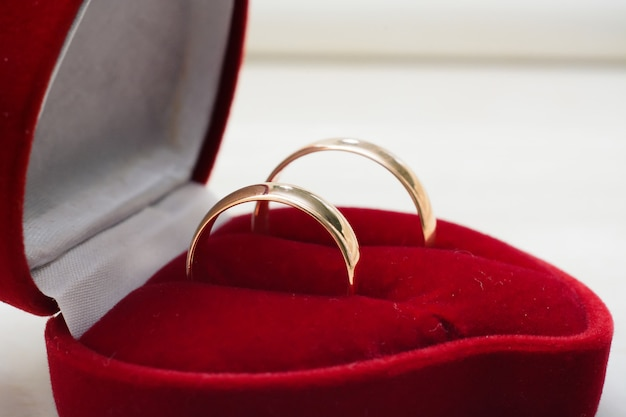 金の結婚指輪のペアは赤いボックスのクローズアップにあります。
