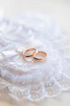 白いレースのクッションに金の結婚式の伝統的なリングのペア