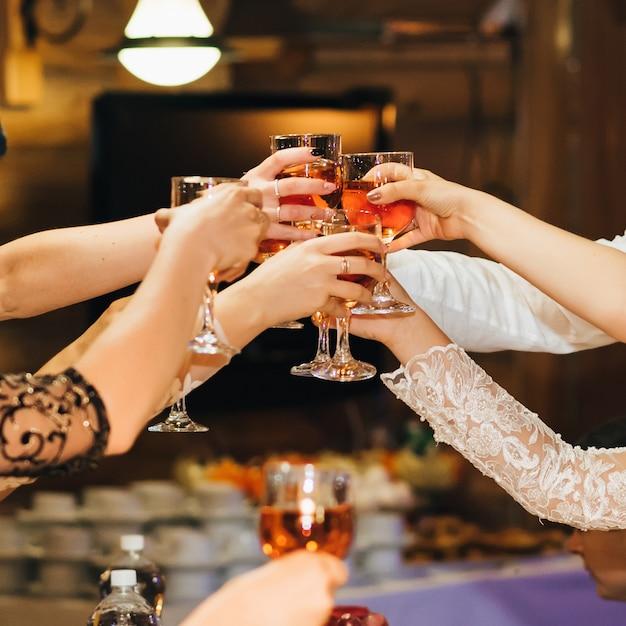 Руки группы людей, звенящих и поджаривающих бокалы с красным вином на праздничной вечеринке в ресторане