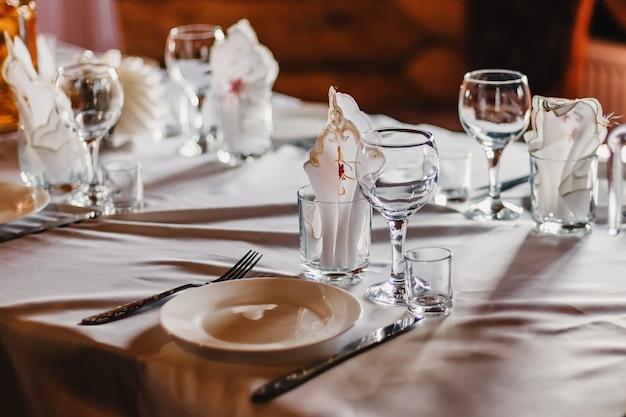 空のグラスとレストランのテーブルの上の白いテーブルクロスにカトラリーとプレートのセット