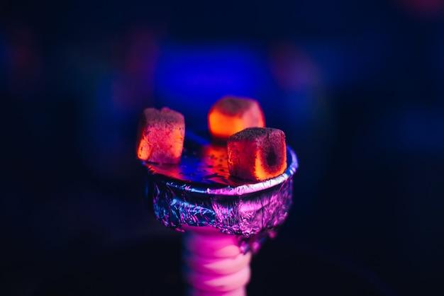 ホイルのシーシャのボウルにたばこの熱い赤い石炭をクローズアップ