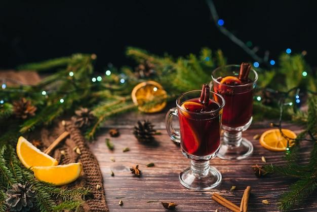 Два бокала с глинтвейном на деревянном столе с еловыми ветками новый год