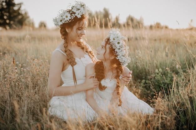幸せな母と娘は笑みを浮かべて、ひもと花の花輪を持つ白いドレスで夏のフィールドにハグ