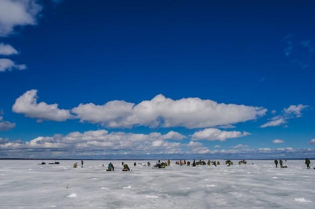 氷の池で釣りをする漁師のグループ