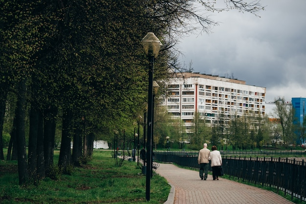 高齢者の祖父と祖母の腕を組んで歩く