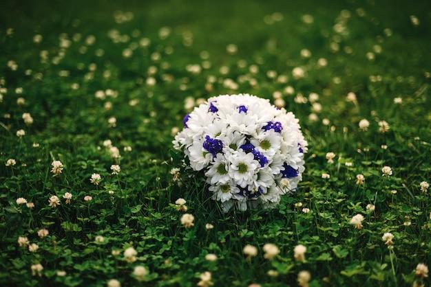 白いヒナギクと横になっている青い花のウェディングブーケ