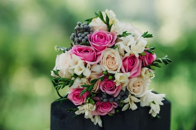 白とピンクのバラと他のカラフルな花のウェディングブーケ